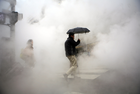 Pedestrians walk through steam coming from grates along a street in New York April 12, 2007. REUTERS/Eric Thayer (UNITED STATES)